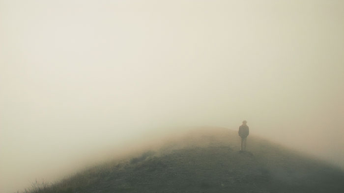 Man atop misty mountain