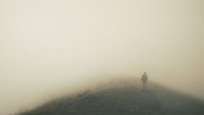 Man atop misty mountain