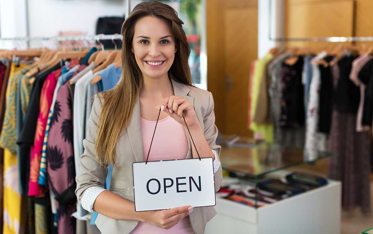 Retail business owner holding Open sign