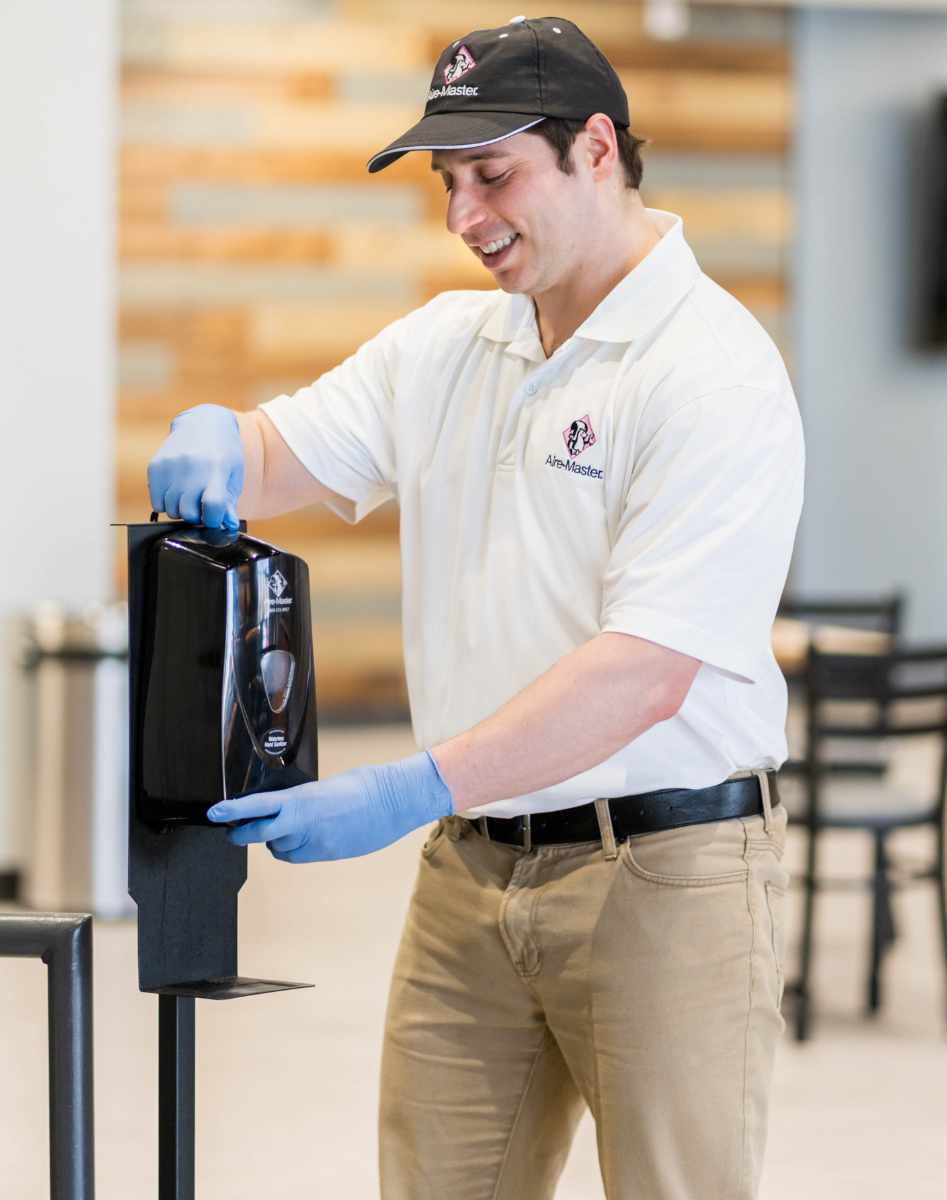 Aire-Master service rep with hand sanitizer dispenser on stand