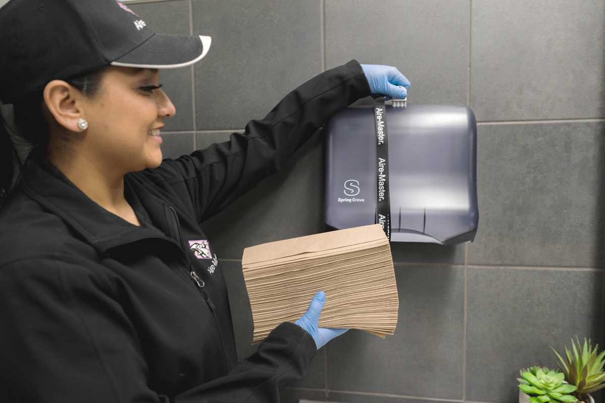 Aire-Master service rep loading paper towels in dispenser