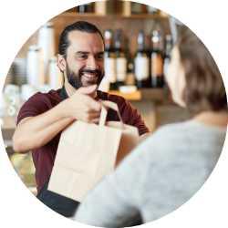 Store clerk handing shopping bag to customer